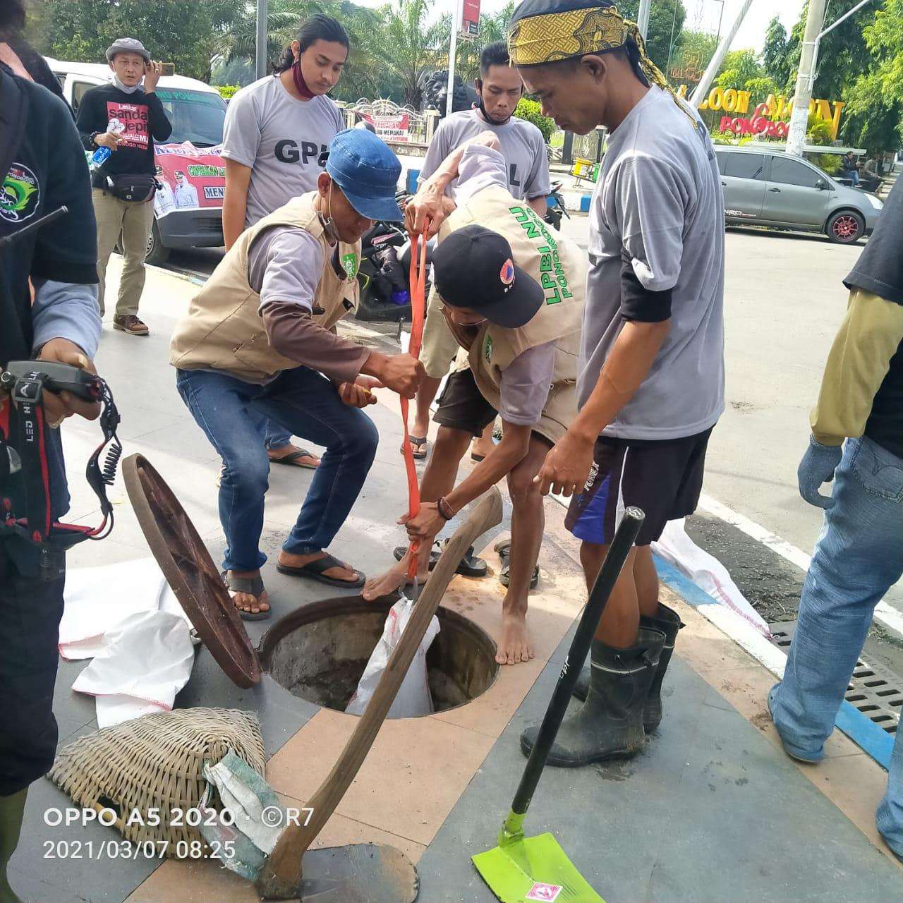 LPBI NU tergabung dengan relawan bersih- bersih sampah dan gorong-gorong air di tengah kota