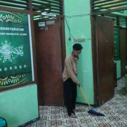 Staf Sekretariat tengah menyapu lantai teras depan kantor sekretariat PCNU