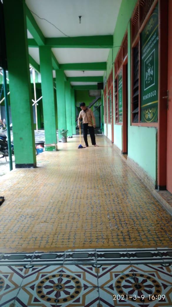 Staf Sekretariat tengah menyapu lantai teras depan ruang Banom PCNU