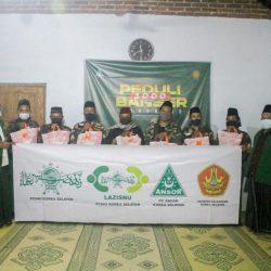 Jajaran Pengurus Cabang Ansor bersama Satkorcab Banser saat memberikan paket sembako di kawasan masjid Tegalsari