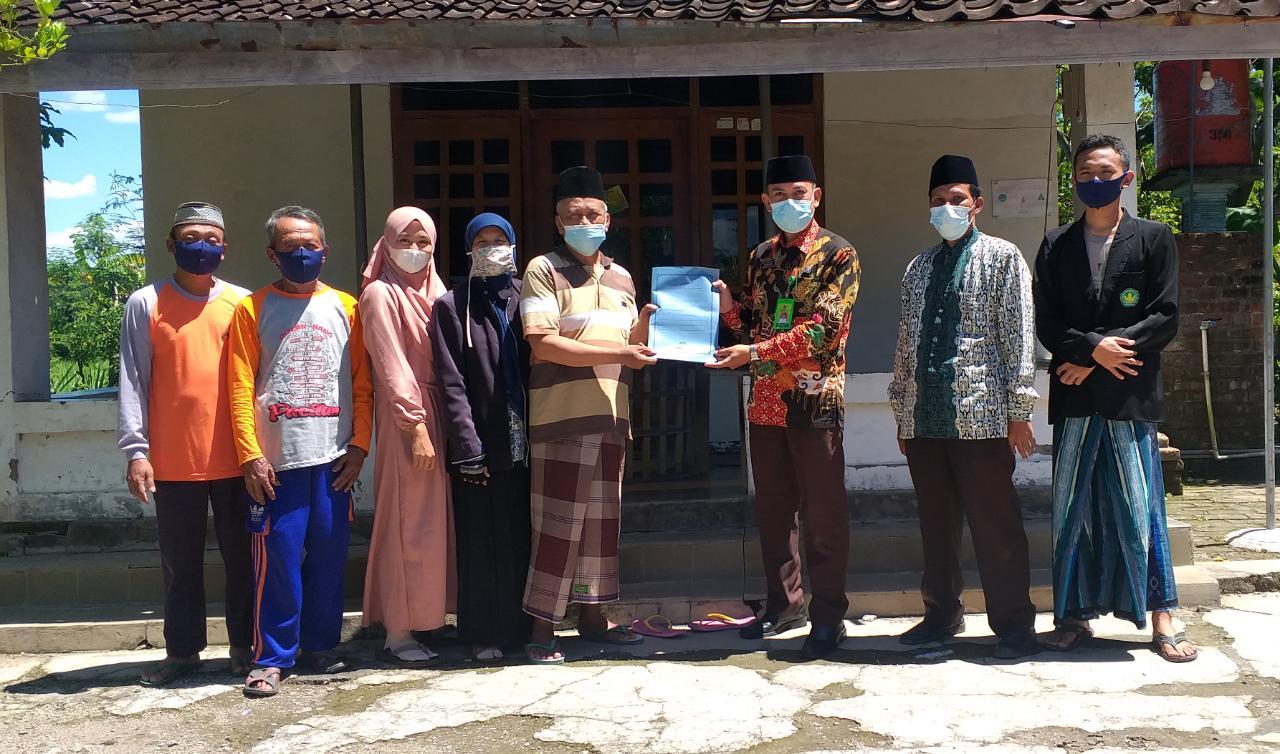 Wakif, PPAIW dan jajaran MWC NU Sawoo berpose bersama usai ikrar wakaf tanah di depan rumah Bambang Margono