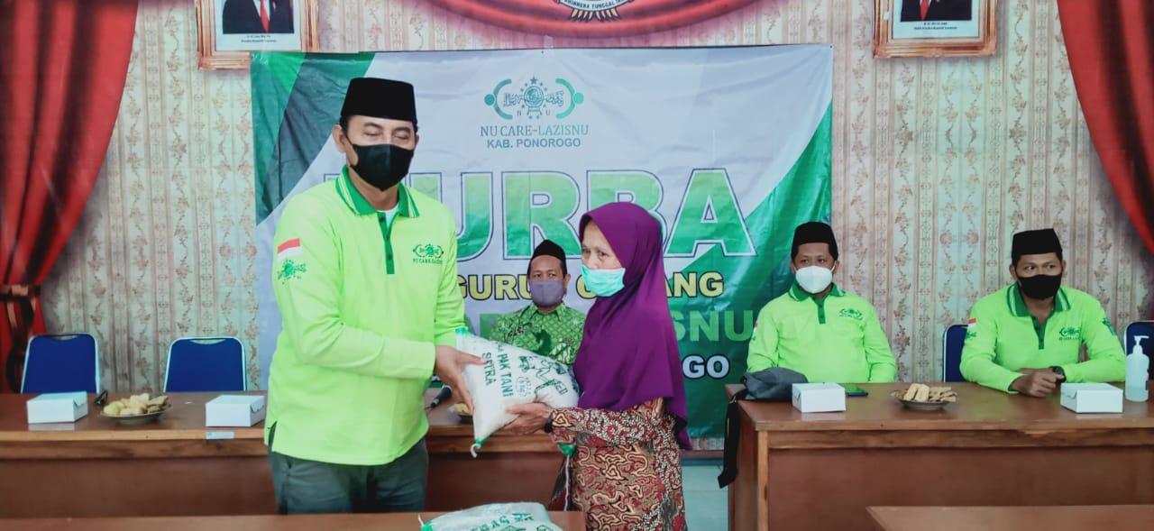 H. Suparlin Direktur Eksekutif NU Care-Lazisnu Ponorogo menyerahkan beras ukuran 5 kg kepada salah satu warga Desa Gedangan