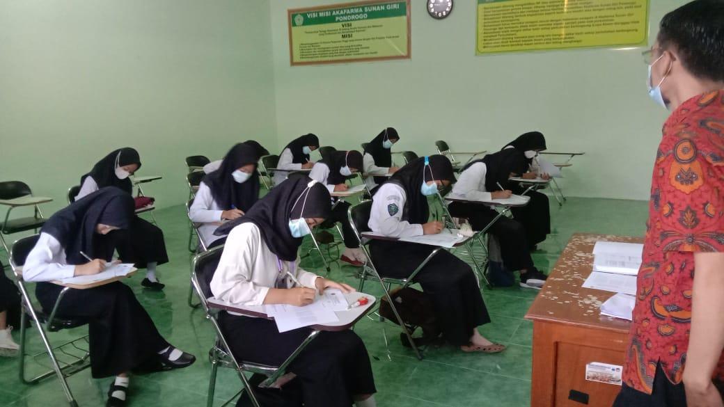 Seorang Pengawas serius mengawasi peserta tes potensi akademik mengerjakan soal