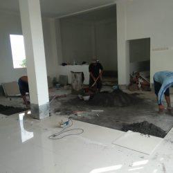 Tiga orang pekerja menyelesaikan pemasangan granit di lantai tiga gedung terpadu PCNU