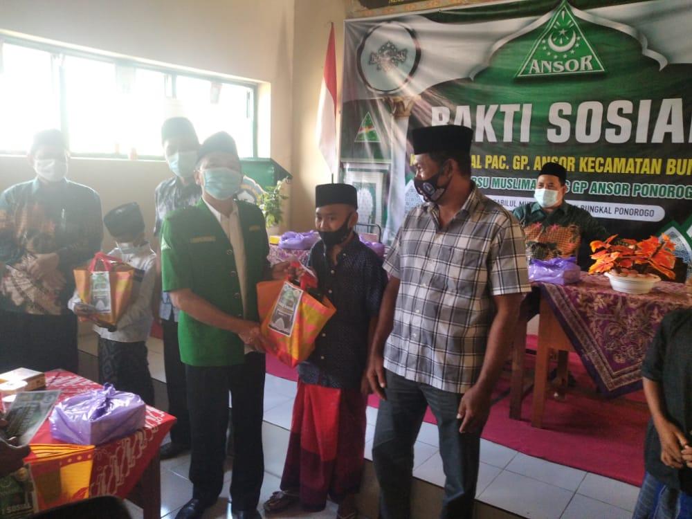 Ketua PC GP Ansor Ponorogo menyerahkan tali asih kepada salah satu peserta khitan