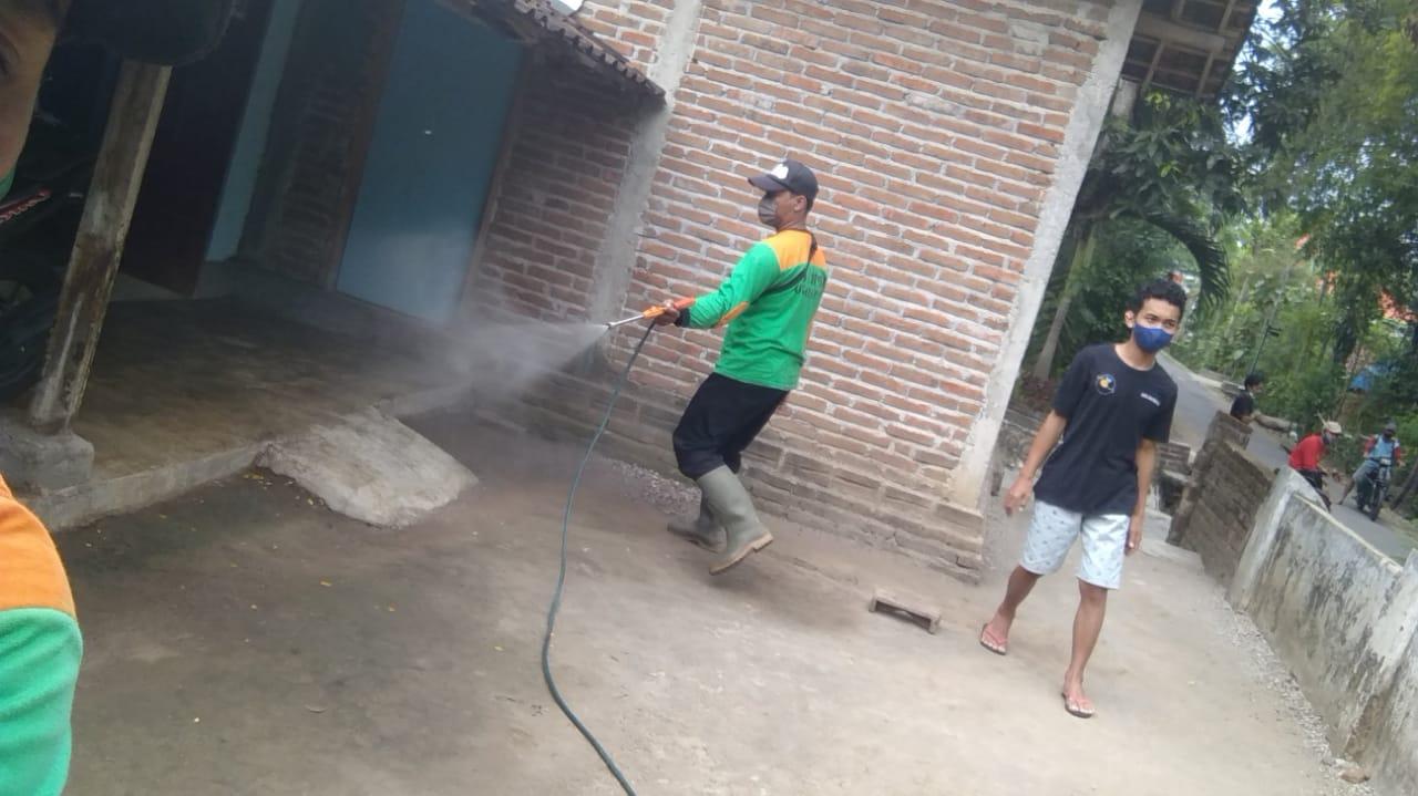 Seorang warga Desa Kapuran mendampingi relawan LPBINU Ponorogo menyemprotkan disinfektan di teras rumahnya