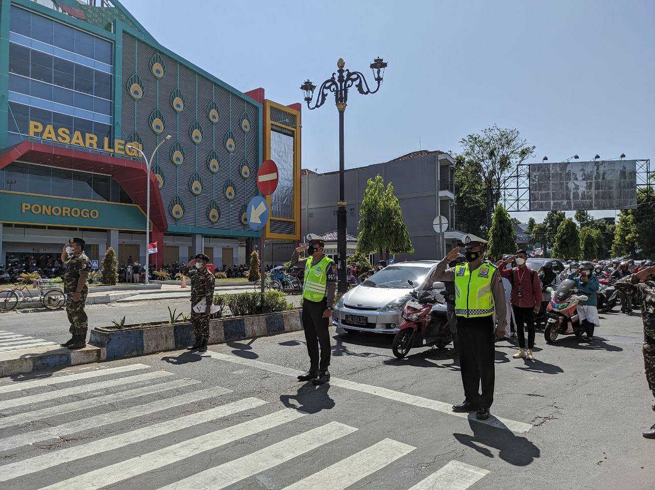 2 Polisi bersama Banser memberi penghormatan kepada bendera merah putih diikuti para pengguna jalan