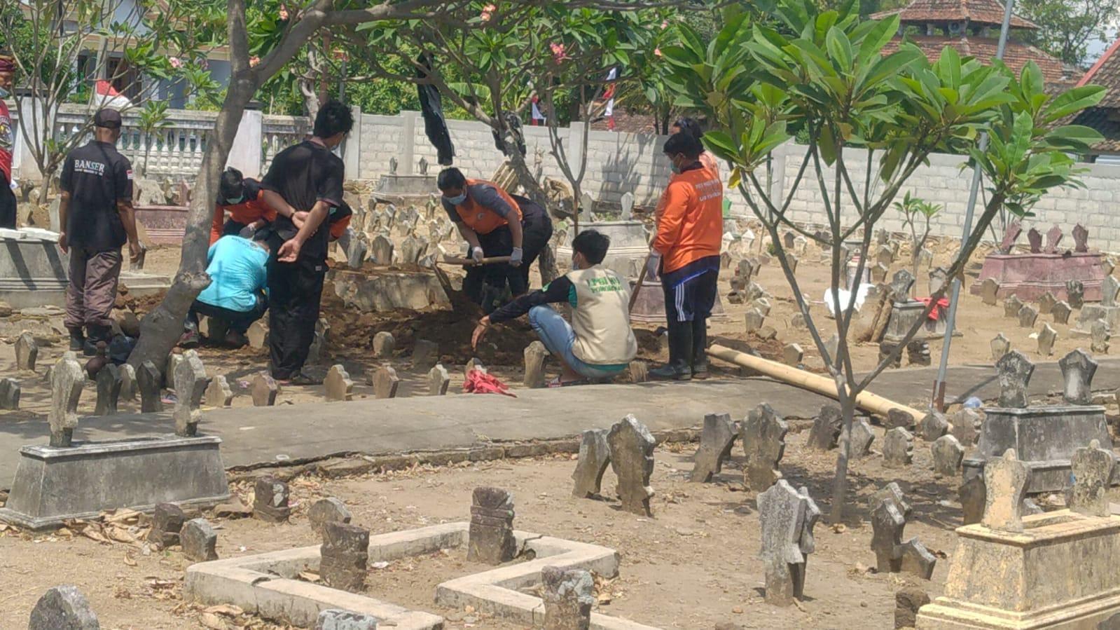 Anggota Banser dan relawan LPBI NU melibatkan diri dalam penimbunan tanah kubur almarhum Mahmudin Asrofi
