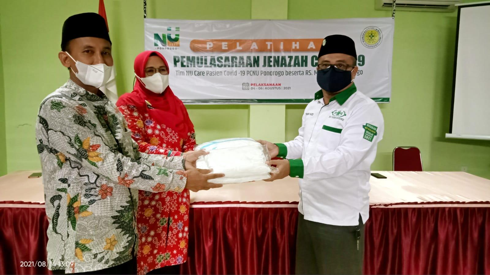 Ketua NU Care-Lazisnu Ponorogo H. Thohir Fauzi menyerahkan secara simbolik seperangkat APD kepada Ketua NU Care-Pasien Covid-19 Agus Khoirul Hadi