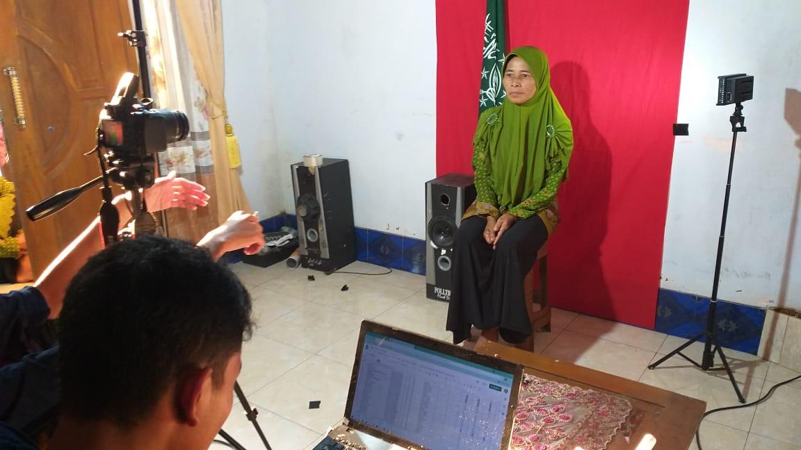 Petugas potografi memberi arahan posisi duduk salah satu anggota Muslimat Pangkal sebelum diambil gambarnya