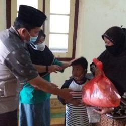 Seorang anak yatim dielus kepalanya oleh salah seorang donatur saat menerima santunan